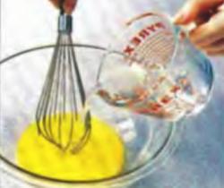 Шаг 6. Добавление горячего сиропа к яичным желткам