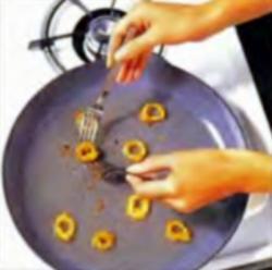 Шаг 9. Переворачивание кусков кальмаров на сковороде